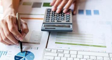 close-up accountant of financieel deskundige analyseren bedrijfsrapportgrafiek en financiëngrafiek op hoofdkantoor. concept van financiële economie, bankbedrijf en beursonderzoek foto