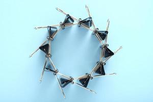 bindmiddel clips in een wielvormige figuur op blauwe achtergrond foto