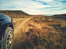 auto op een onverharde weg foto