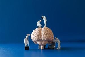 miniatuurmensen, wetenschappers die het menselijk brein observeren en bespreken, medische gezondheidszorg en chirurgisch doktersserviceconcept. foto