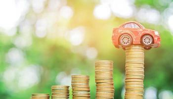 rode auto op muntstuk natuurlijke onscherpe achtergrond. concept van autoverzekering foto