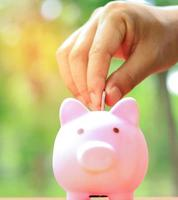 hand zetten spaarvarken en munt met natuurlijke onscherpe achtergrond, concept geldbesparing voor het kopen van een auto foto