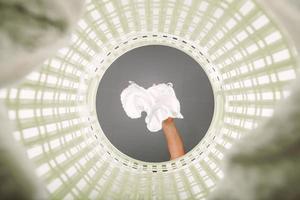 witte doek in de mand gegooid om te wachten op het wassen. uitzicht vanaf de binnenkant van de mand. foto