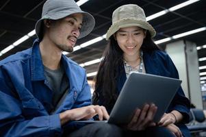 zakenman zit en gebruikt laptop om te werken op de luchthaven, jongere gaat op reis en heeft internetcommunicatietechnologie voor werk tijdens het wachten binnen bij vertrek van de luchthaven foto