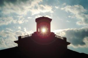 silhouet van een oud gebouw met zonnestralen in het raam tegen de avondrood foto