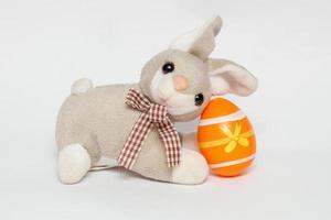 grijs pluche konijn met klein oranje plastic ei, gebruikt voor paasdecoratie foto
