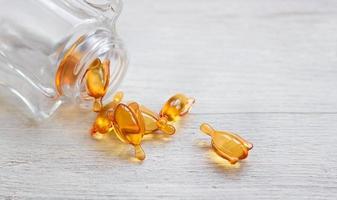 huid en haar vitamine serum oranje capsules op witte tafel foto