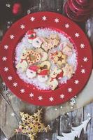 kerstkoekjes op rode feestelijke plaat met sneeuwvlokken foto