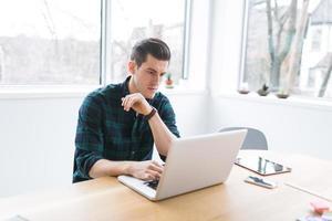 jonge man met behulp van een laptop foto