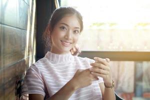 Aziatische vrouw met behulp van slimme telefoon aan een tafel foto