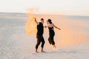 jongen en een meisje in zwarte kleren knuffelen en rennen op het witte zand met oranje rook foto