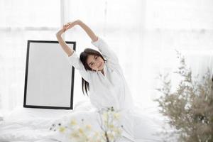 Aziatische vrouw die zich uitstrekt in bed foto