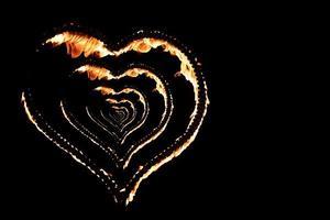 brandend hart met vlammen geïsoleerd op donkere achtergrond foto