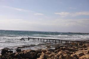 stenen strand met oude houten ponton in de buurt van de zee-achtergrond foto