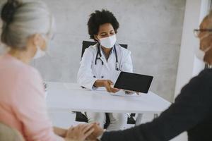 gemaskerd ouder paar dat nieuws van de dokter ontvangt foto