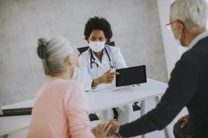 ouder paar in maskers in gesprek met de arts foto