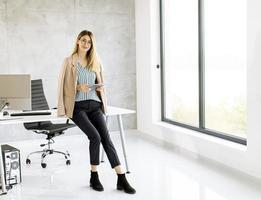 zakenvrouw zittend op de rand van een bureau met een tablet foto
