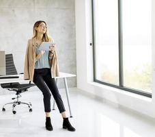zakenvrouw kijkt uit raam en houdt een tablet vast foto