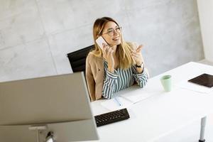 zakenvrouw op telefoon bij bureau foto