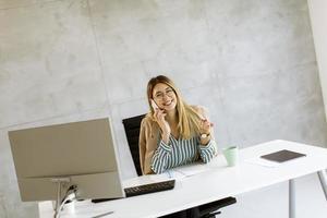 zakenvrouw op telefoon bij bureau met kopie ruimte foto