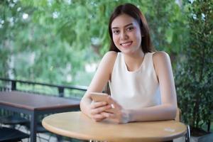 vrouw buiten zitten met behulp van slimme telefoon foto