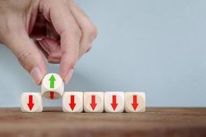 hand veranderen met omdraaien verandert de richting van een pijl op houten kubus bedrijfsconcept voor innovatieve oplossing foto
