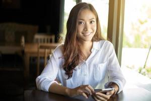 vrouw met behulp van slimme telefoon in een café foto