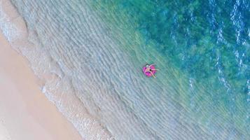 luchtfoto bovenaanzicht van drone-weergave van jongen met zwemring in de zee en schaduw smaragdblauw water en golfschuim bij zonsopgang foto