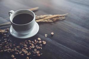 koffieboon en zwarte koffiekopje op houten bureau bij coffeeshop - vintage effect. foto