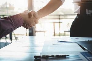 zakenlieden slaan de handen ineen in zaken tussen bedrijven om hun zakelijk potentieel te vergroten foto