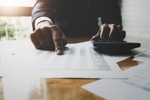 zakenman met behulp van rekenmachine met beursgegevens grafiek en belasting- en budgetpapier in kantoor te berekenen foto