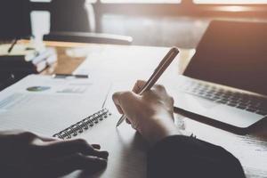 secretaresse of bedrijfsmedewerker houdt de pen vast om aantekeningen te maken op het notitieblok tijdens de vergadering met het gebruik van het budgetgegevensdocument en de laptop om gegevens te analyseren foto