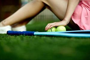 meisje, zittend op het gazon van een tennisveld met een tennisracket foto