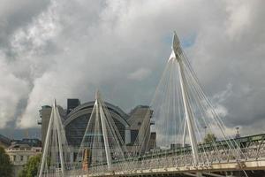 uitzicht op de gouden jubileumbruggen en het Charing Cross-station vanaf de zuidkust van de rivier de Theems in Londen op een bewolkte zomerdag foto