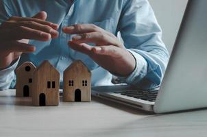 onroerend goed verzekering concept bedrijf. zakenman handen op huis en computer laptop. eigendom veiligheidsconcept. foto
