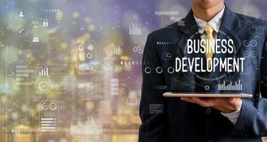 zakenman die een tabletcomputer, goed baanpictogram, grafieken, abstracte achtergrond met bokeh houdt. foto