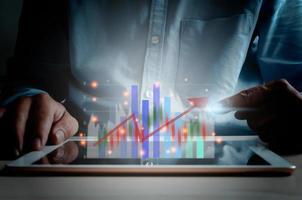zakelijke financiën en technologie. investeringsconcept. investeren in de aandelenmarkt en fondsen. zakenman analyseert financiële gegevens, grafieken en forexhandel op een tablet. foto