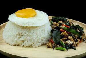 rijst gegarneerd pittig gebakken varkensvlees met basilicum topping, gebakken eieren op een houten schotel, pad krapow moo is traditioneel thais eten foto