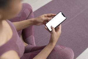 vrouw op yogamat met behulp van smartphone foto
