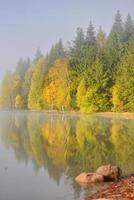 herfst landschap in de bergen met bomen weerspiegelen in het water bij st ana lake roemenië foto