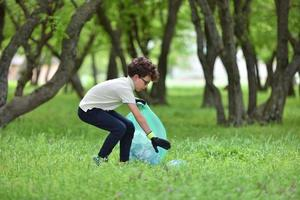 jonge jongen pikt afval op in een lentebos bij zonsondergang foto