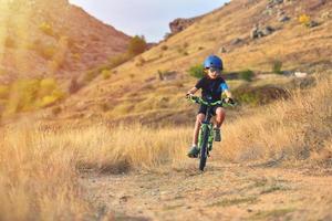 gelukkig kind plezier in herfst park met een fiets op mooie herfstdag foto