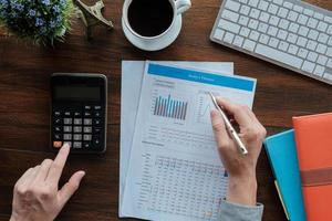boekhoudkundige bedrijfsconcept, zakenman met behulp van pen wijzend met voorraad maket gegevens financiële grafiek en rekenmachine voor het berekenen van budget planner papier in kantoor. foto