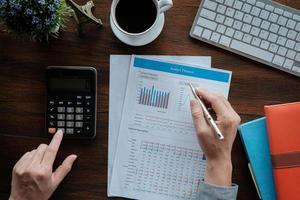 boekhoudkundige bedrijfsconcept, zakenman met behulp van pen wijzend met gegevens budget planner grafiek en rekenmachine voor het berekenen van financieringsplan papier in kantoor. foto
