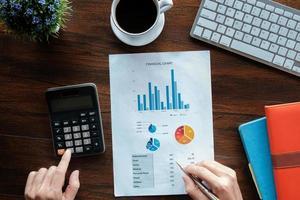 boekhoudkundige bedrijfsconcept, zakenman met behulp van pen wijzend met voorraad maket gegevens financiële grafiek en rekenmachine voor het berekenen van financiële plan papier in kantoor. foto