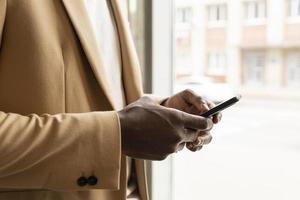 man houdt een telefoon vast met in beige pak foto