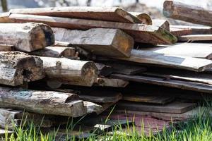 een stapel oude houten planken op de grond foto