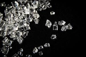witte suikerkristallen op een zwarte achtergrond foto