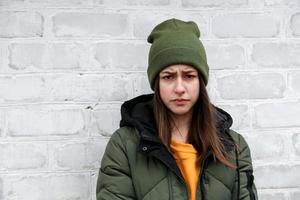portret van een mooi verdrietig meisje in een gele trui en kaki hoed foto