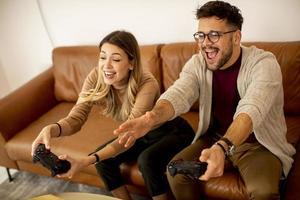 jong koppel spelen van videogames thuis zittend op de bank en genieten foto
